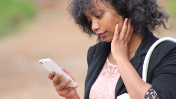 femme afro regarde téléphone